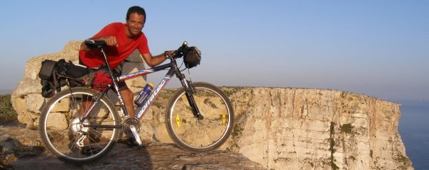 Gerald Grech with his bicycle on a mountaintop in Malta, Europe
